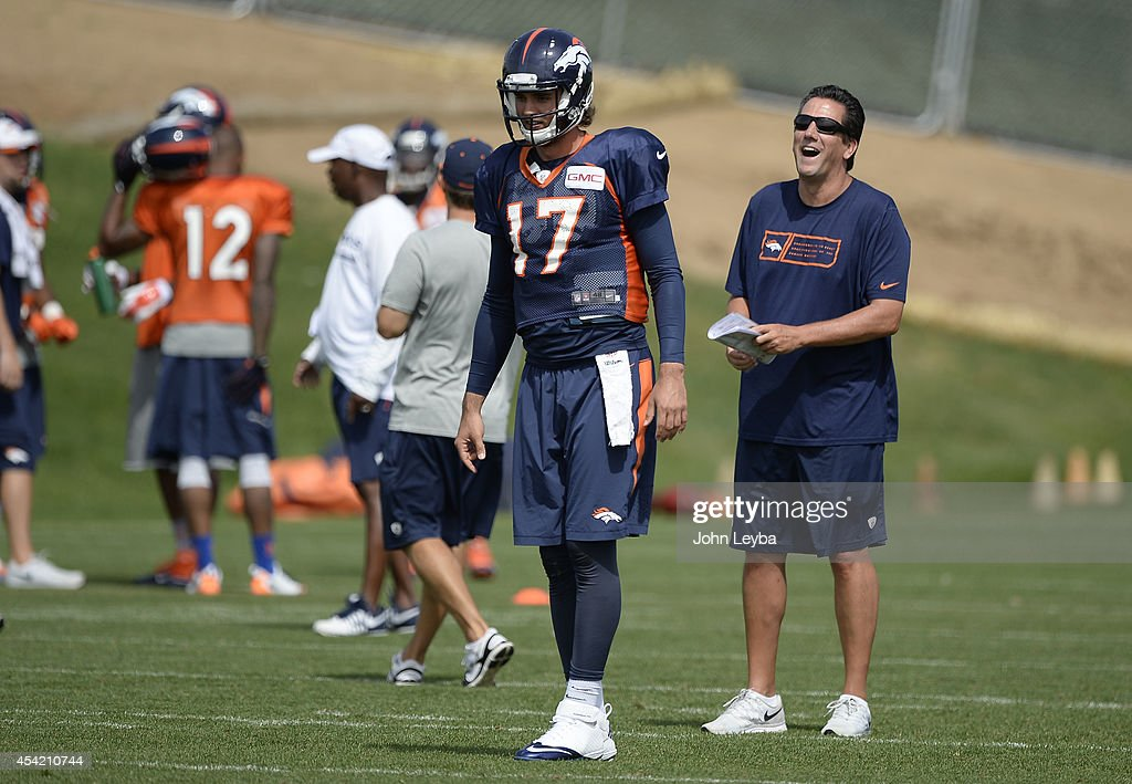 Denver Broncos quarterbacks coach <a gi-track='captionPersonalityLinkClicked' href=/galleries/search?phrase=Greg+Knapp&family=editorial&specificpeople=750404 ng-click='$event.stopPropagation()'>Greg Knapp</a> laughs out during drills as Denver Broncos quarterback <a gi-track='captionPersonalityLinkClicked' href=/galleries/search?phrase=Brock+Osweiler&family=editorial&specificpeople=6501030 ng-click='$event.stopPropagation()'>Brock Osweiler</a> (17) prepares for the snap during practice August 26, 2014 at Dove Valley.