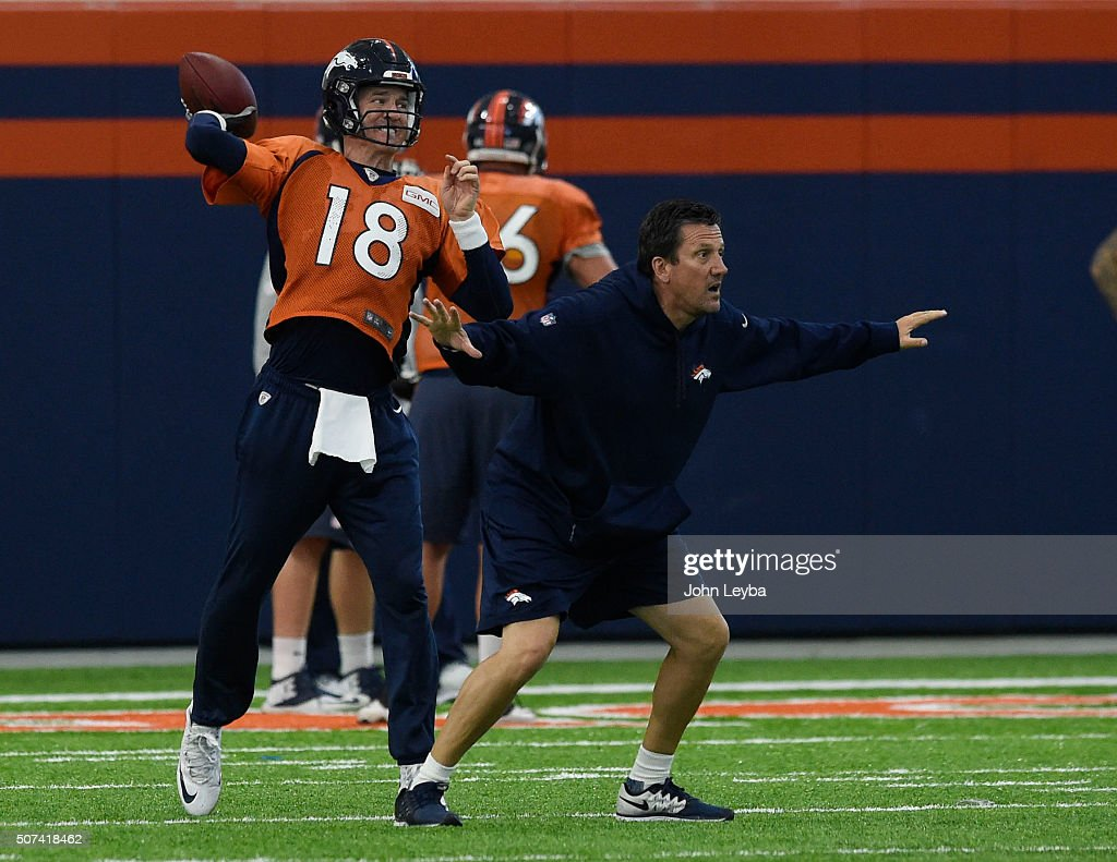 Denver Broncos quarterbacks coach <a gi-track='captionPersonalityLinkClicked' href=/galleries/search?phrase=Greg+Knapp&family=editorial&specificpeople=750404 ng-click='$event.stopPropagation()'>Greg Knapp</a> provides protection for Denver Broncos quarterback <a gi-track='captionPersonalityLinkClicked' href=/galleries/search?phrase=Peyton+Manning&family=editorial&specificpeople=184524 ng-click='$event.stopPropagation()'>Peyton Manning</a> (18) as runs through drills during practice January 29, 2016 at UCHealth Training Center.