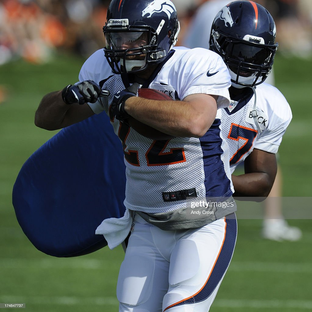 Denver Broncos RB, Jacob Hester, left, gets past fellow running back, Knowshon Moreno, right, on a running drill during training camp at Dove Valley Saturday July 26, 2013.