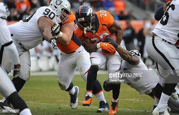 Denver Broncos running back Justin Forsett gets tackled by Oakland Raiders Dan Williams and Brue Irvin in the second quarter at Sports Authority...