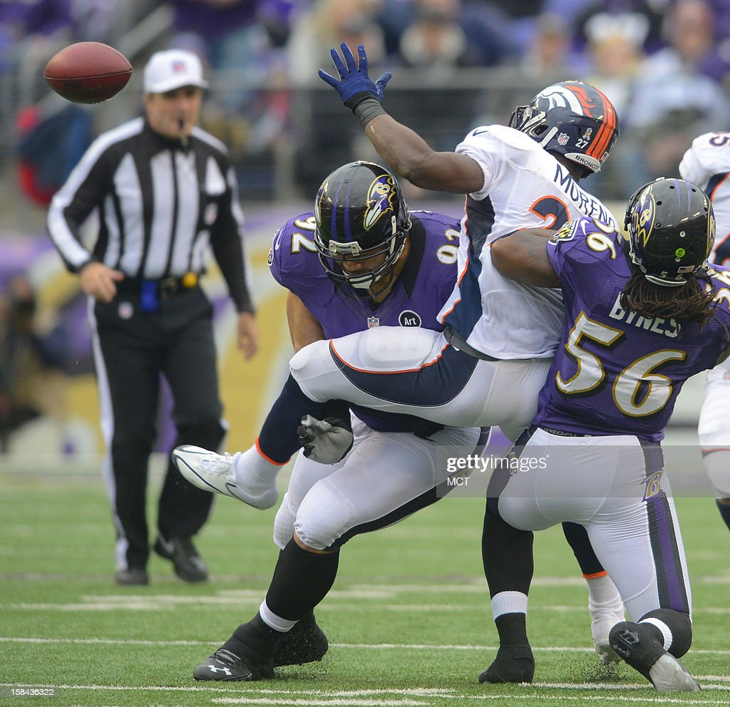 Denver Broncos running back Knowshon Moreno is separated from the ball by Baltimore Ravens defensive end Haloti Ngata and linebacker Josh Bynes during the first half of their game in Baltimore, Maryland, on Sunday, December 16, 2012.