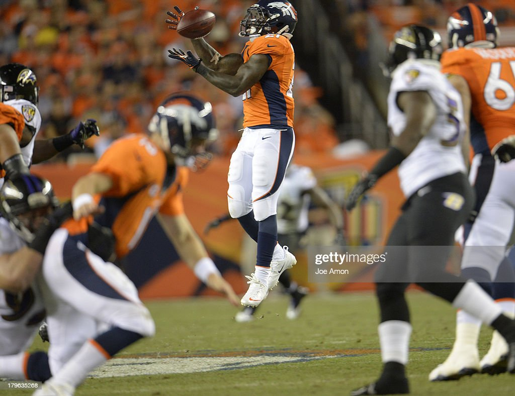 Denver Broncos running back Ronnie Hillman (21) makes a first down catch in the third quarter, why Denver Broncos quarterback Peyton Manning (18) gets taken down in the foreground.. Denver Broncos Baltimore Ravens September 5, 2013 at Sports Authority at Mile High.