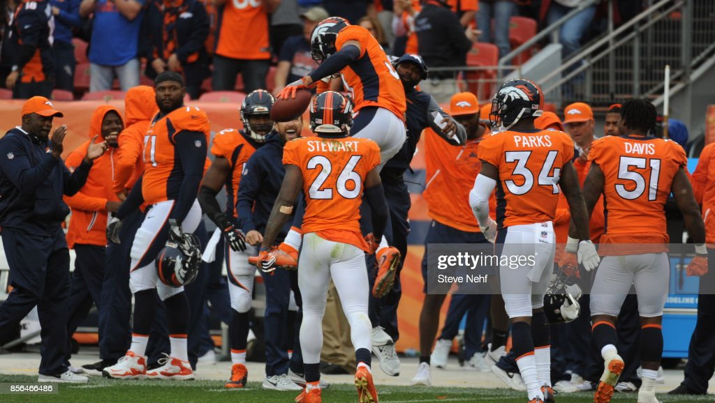 Denver Broncos safety Justin Simmons and defensive backs coach Marcus Roberston celebrate the game-clinching interception by Simmons against the Oakland Raiders in the fourth quarter at Sports Authority Field at Mile High on Sunday, October 1, 2017.
