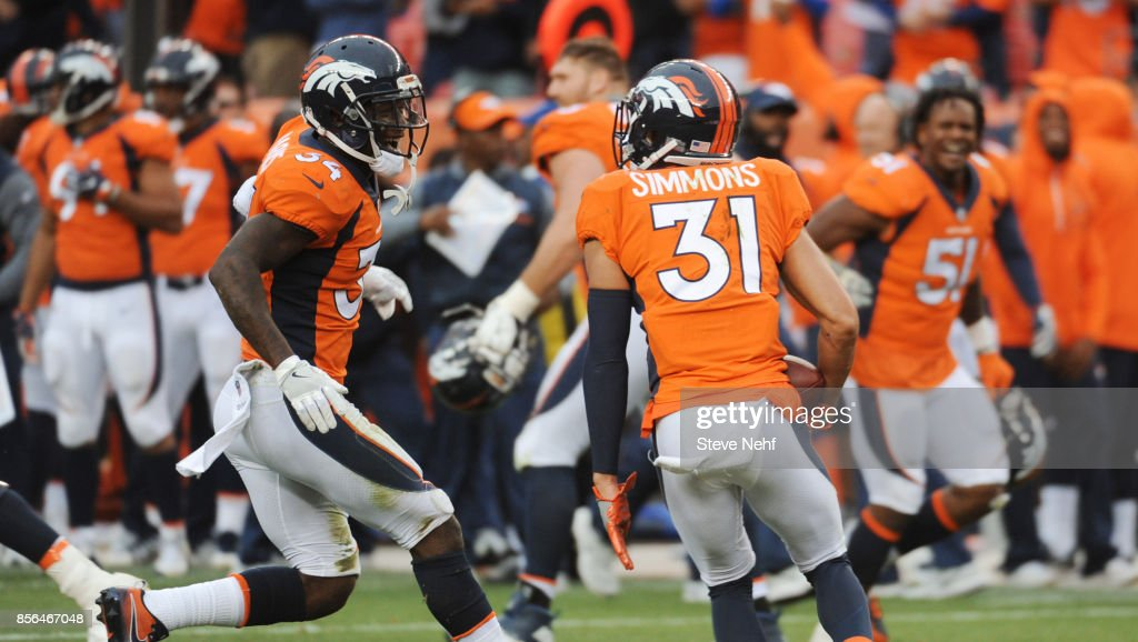 Denver Broncos safety Will Parks, left, celebrates Justin Simmons' interception of Oakland Raiders quarterback E.J. Manual to seal the victory in the fourth quarter at Sports Authority Field at Mile High on Sunday, October 1, 2017.
