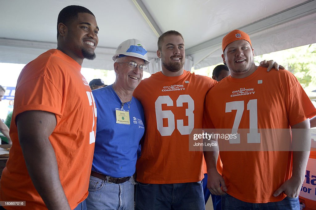 Denver Broncos tackle Chris Clark (75) Ben Garland (63) and Paul Cornick (71) pose with Volunteer Bill Ross as players join together to pay a visit to 30th annual Jimmy & Rosalynn Carter Work Project October 9, 2013 at the Globeville project.
