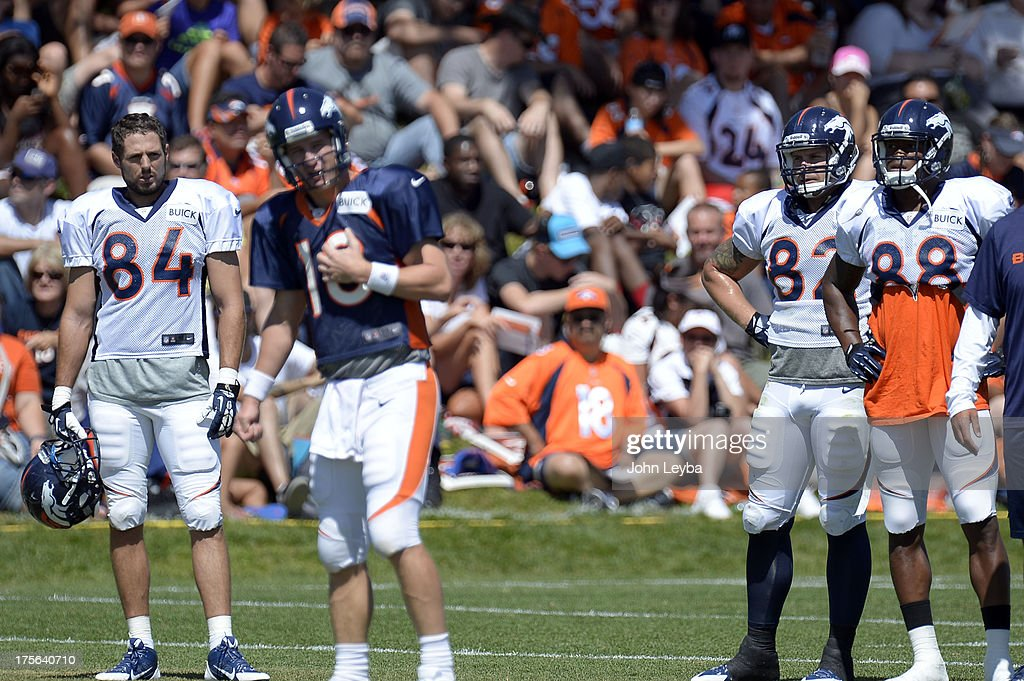 Denver Broncos TE Jacob Tamme (84) Jake O'Connell (82) and WR Demaryius Thomas watch QB Peyton Manning (18) run the offense during training camp August 5, 2013 at Dove Valley.