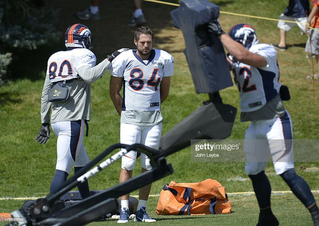 Denver Broncos TE Julius Thomas (8) pats Jacob Tamme (84) on the shoulder as he watches Jake O'Connel (82) in drills during training camp August 5, 2013 at Dove Valley.