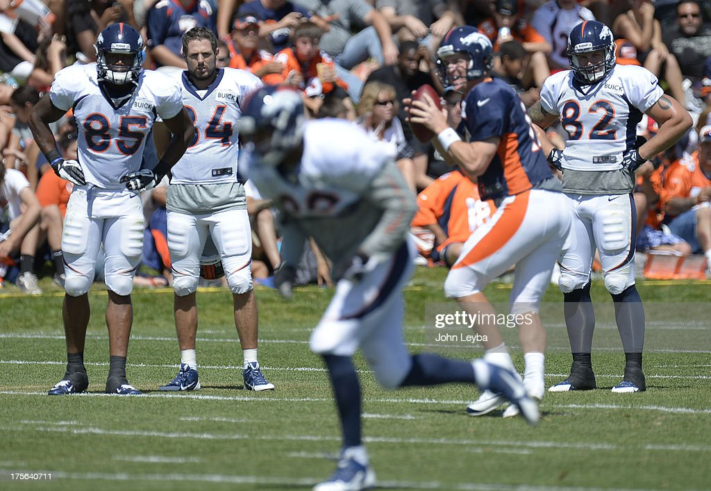Denver Broncos TE Virgil Green (85) Jacob Tamme (84) Jake O'Connell (82) watch QB Peyton Manning (18) run the offense with TE Julius Thomas running his route during training camp August 5, 2013 at Dove Valley.