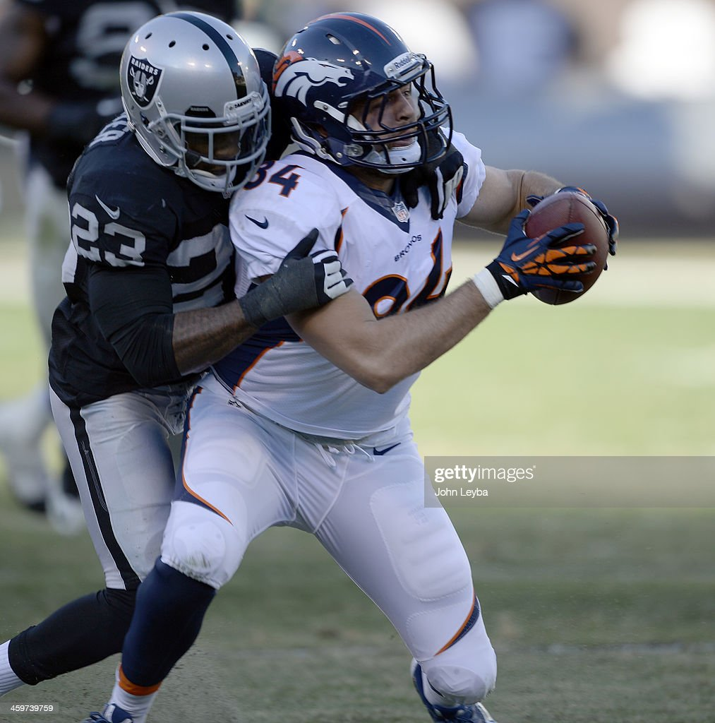 Denver Broncos tight end Jacob Tamme (84) gets caught from behind by Oakland Raiders cornerback Tracy Porter (23) after a short gain during the third quarter at O.co Coliseum.