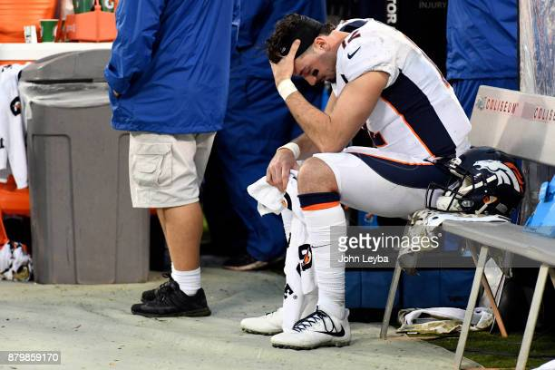 Denver Broncos training staff looks over quarterback Paxton Lynch sits dejected on the bench in the fourth quarter against the Oakland Raiders on...