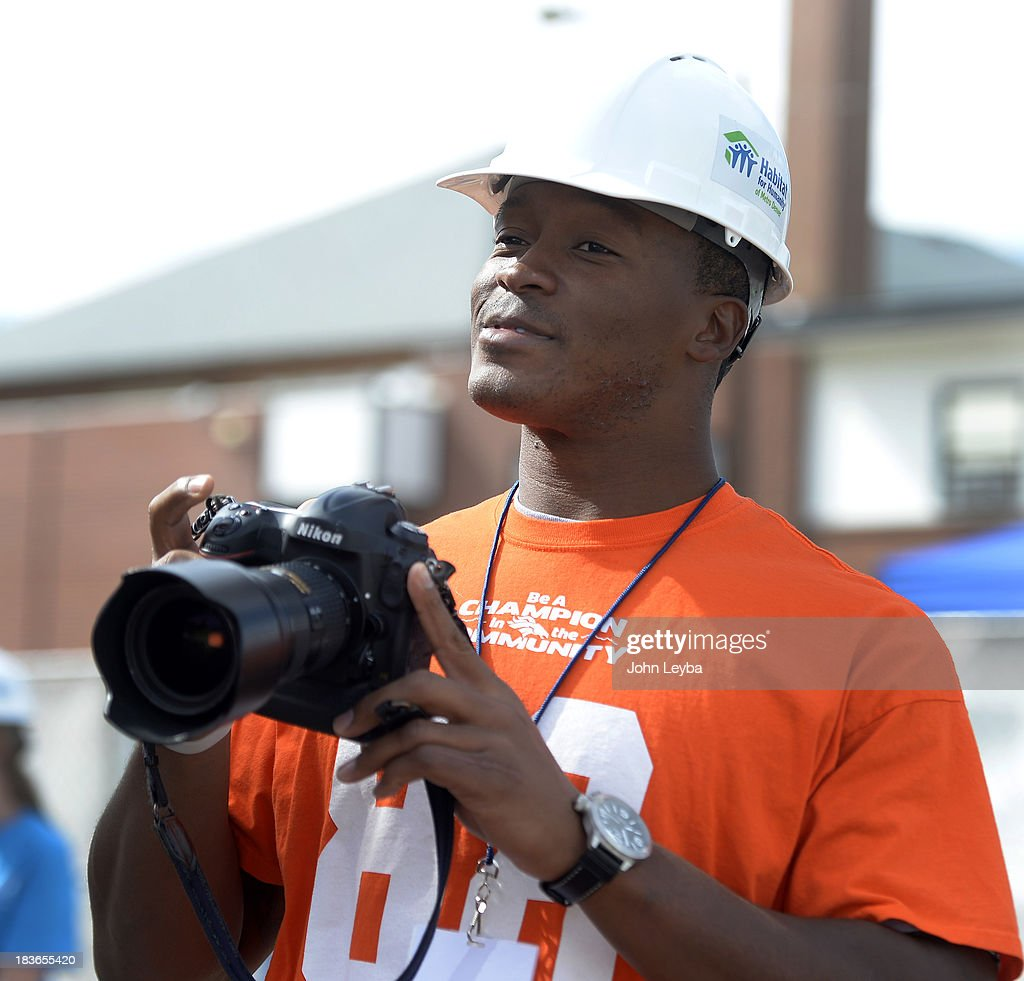 Denver Broncos wide receiver Demaryius Thomas (88) tries his hand at photography as players join together to pay a visit to 30th annual Jimmy & Rosalynn Carter Work Project October 9, 2013 at the Globeville project.