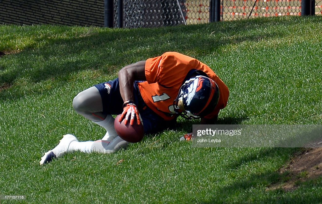 Denver Broncos wide receiver Lamaar Thomas (19) lays on the grass in pain after going down with an injury after catching a pass during practice August 22, 2013 at Dove Valley