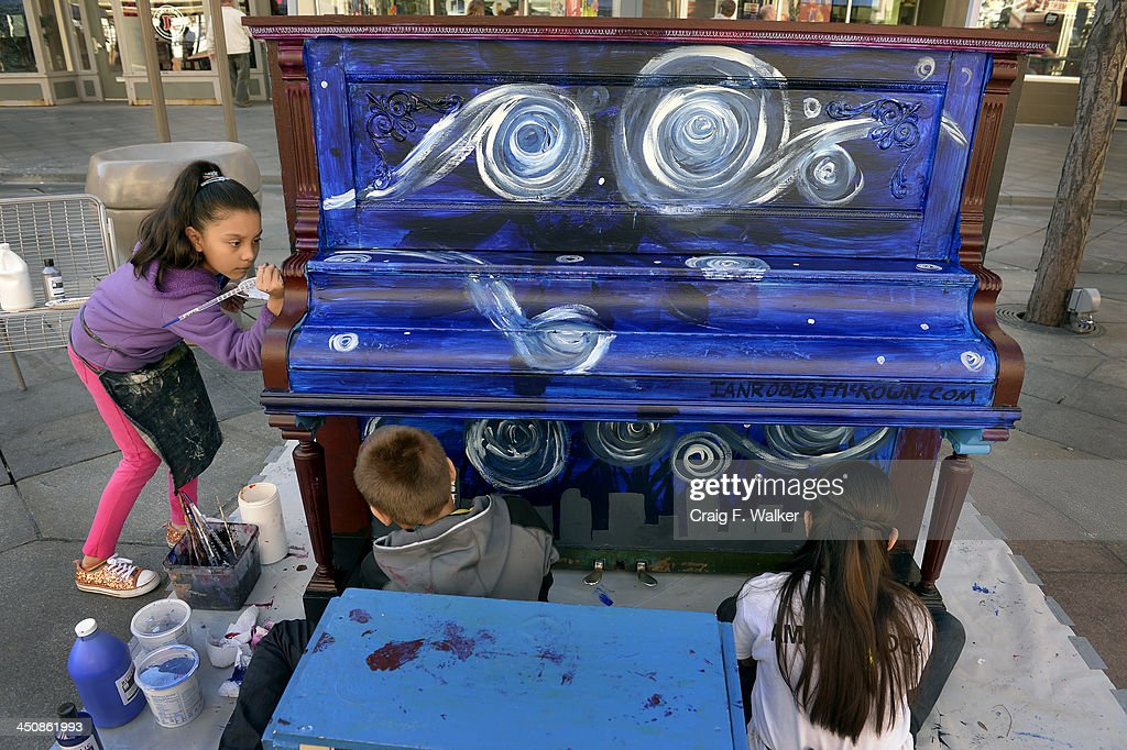 Denver Center for International Studies fourth grader Estefany Munoz, left, joins her classmates in painting a piano on the 16th Street Mall in Denver, CO November 20, 2013. DCSI students volunteered to paint 5 pianos for the a public art installation, Your Keys to the City. The winter themed pianos will be unveiled on Thanksgiving and will be placed on the mall through the end of the year.
