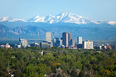 Snow covered Longs Peak, part of the Rocky Mountains stands tall in the background with green trees and the Downtown Denver skyscrapers as well as hotels, office buildings and apartment buildings fill