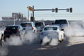 At a busy intersection with traffic signals and stop lights in Denver, Colorado on a winter day, exhaust pours out of tailpipes from accelerating cars, trucks, and other vehicles as they drive onto a