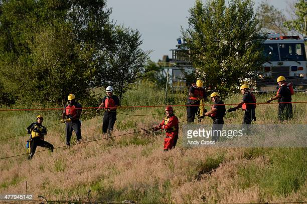 Denver Fire Dept Water Rescue team and Denver Firefighters anchor ropes across the South Platte during a search for a reported tubing accident victim...