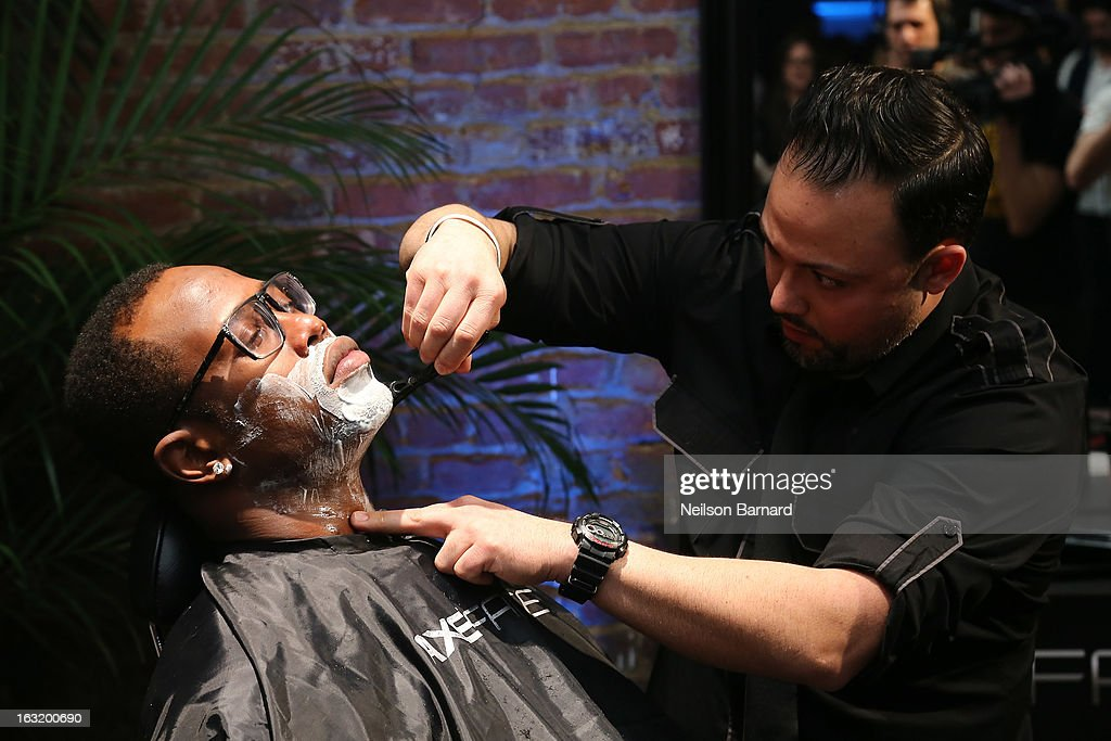 Denver linebacker Von Miller (L) gets a clean shave at the AXE Facescore event at Drive-In Studio on March 5, 2013 in New York City.