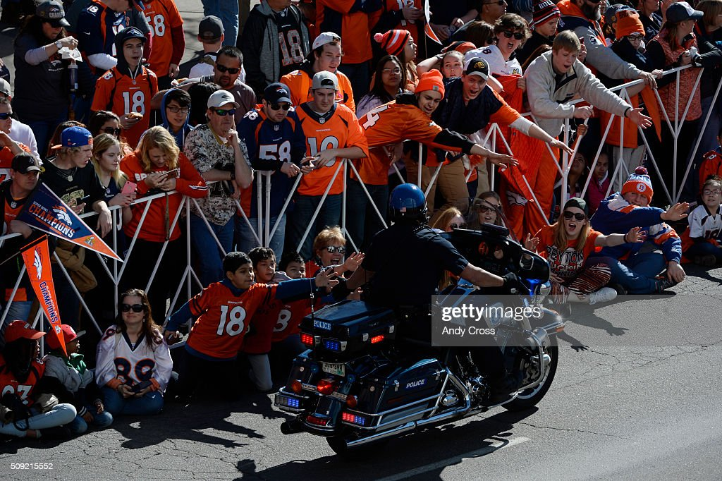 A Denver Motorcycle police officer high-fives Denver Broncos fans gathered for the Denver Broncos Super Bowl 50 celebration parade February 07, 2016.