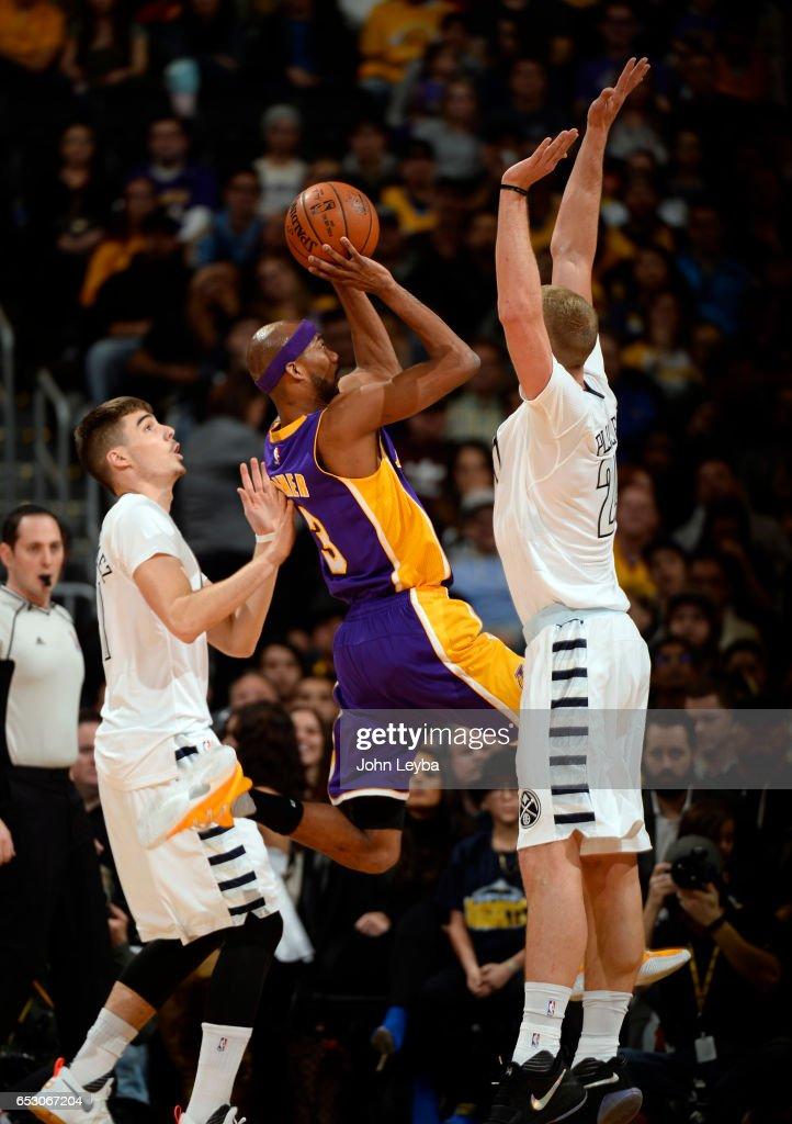 Denver Nuggets center Mason Plumlee (24) blocks a shot by Los Angeles Lakers forward Corey Brewer (3) during the first quarter on March 13, 2017 in Denver, Colorado at Pepsi Center.