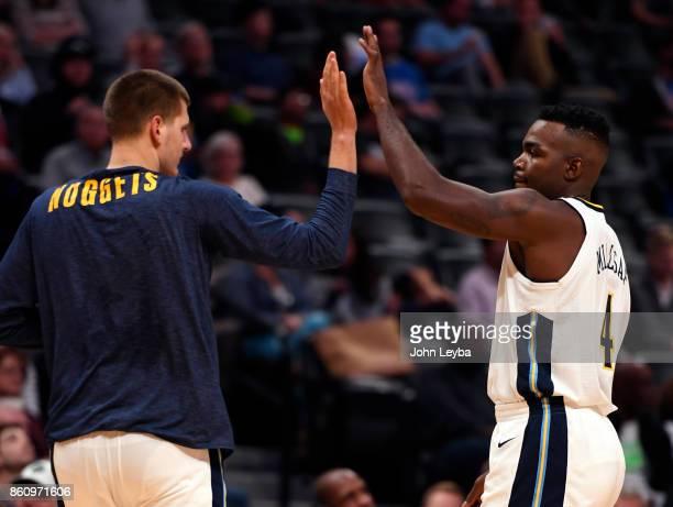 Denver Nuggets center Nikola Jokic high fives Denver Nuggets forward Paul Millsap during a timeout against the Oklahoma City Thunder on October 10...