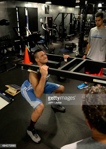 Denver Nuggets Danilo Gallinari grimaces as he goes through a rigorous workout with assistant coach/strength and conditioning Steve Hess May 27 2014...