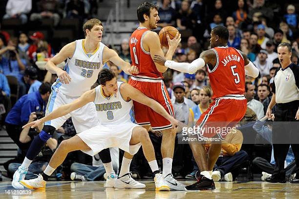 Denver Nuggets forward Danilo Gallinari loses his footing as he and teammate Timofey Mozgov guard Milwaukee Bucks center Andrew Bogut and shooting...