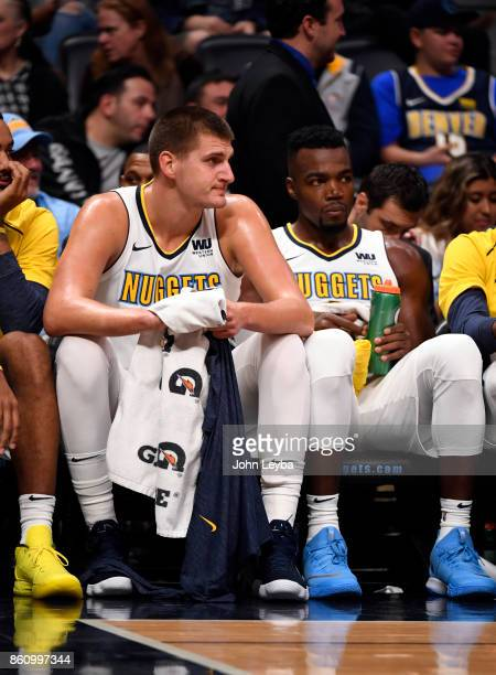 Denver Nuggets forward Paul Millsap and center Nikola Jokic sit on the bench in the fourth quarter against the Oklahoma City Thunder on October 10...