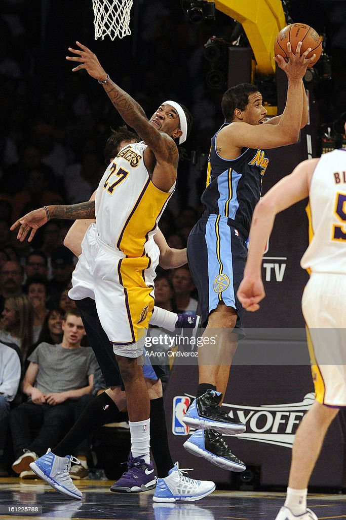 Denver Nuggets point guard Andre Miller grabs a rebound away from Los Angeles Lakers center Jordan Hill during the second half of the Lakers' 10388...