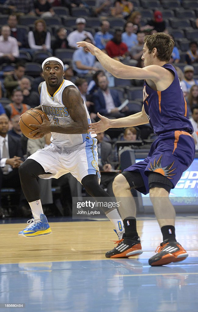 Denver Nuggets point guard Ty Lawson (3) looks to pass as Phoenix Suns point guard Goran Dragic (1) defends on the play during the first quarter October 23, 2013 at Pepsi Center.