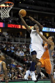 Denver Nuggets point guard Ty Lawson takes lays the ball up over Phoenix Suns point guard Shannon Brown during a game at the Pepsi Center on Tuesday...