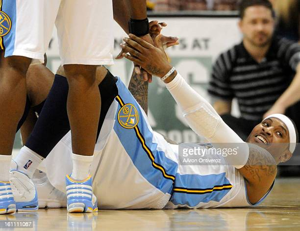 Denver Nuggets small forward Carmelo Anthony smiles as he gets helped up after being fouled by Houston Rockets shooting guard Kevin Martin during the...
