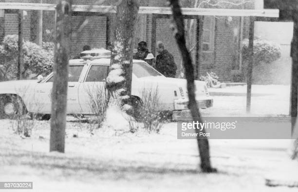 Denver officers hustle the suspect in white hat to a waitig police car well away from the gathered media after she surrendered to officers folowing...