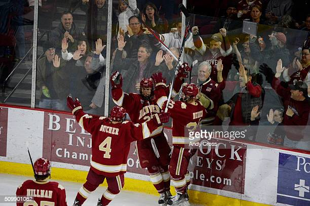 Denver Pioneers center Quentin Shore celebrates his goal against North Dakota with Denver Pioneers defenseman Will Butcher and Denver Pioneers...