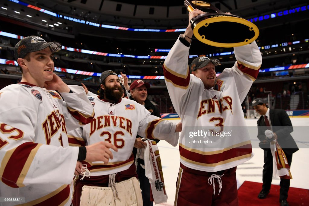 Denver Pioneers defenseman Tariq Hammond (3) raises the trophy after their win over the Minnesota-Duluth Bulldogs 3-2 in the NCAA Men's Ice Hockey Championship on April 8, 2017 in Chicago, Illinois at the United Center. Hammond left the game with a leg injury. Denver Pioneers forward Troy Terry (19) and Denver Pioneers goalie Tanner Jaillet (36) stand by his side.