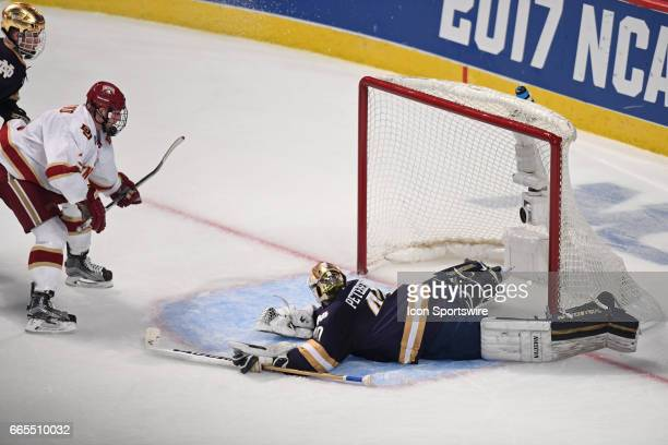 Denver Pioneers defenseman Tariq Hammond watches his goal against Notre Dame Fighting Irish goalie Cal Petersen in the second period of an NCAA...