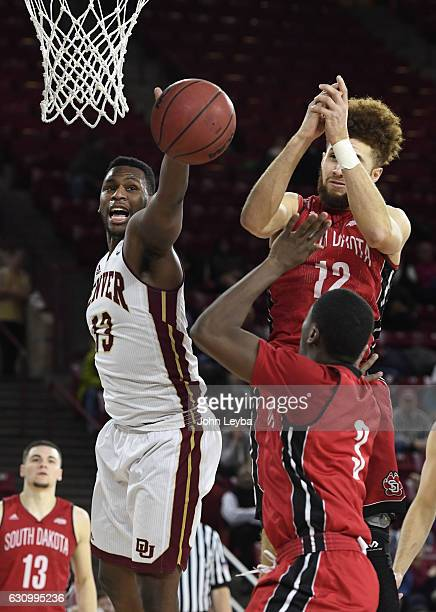 Denver Pioneers forward CJ Bobbitt battles for the rebound with South Dakota Coyotes forward Trey BurchManning and South Dakota Coyotes guard Triston...