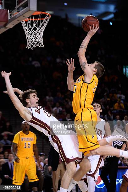 Denver Pioneers forward Dom Samac gets called for a foul as Wyoming Cowboys guard Nathan Sobey drives to the basket during the first half December 15...