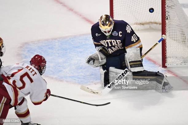 Denver Pioneers forward Evan Ritt scores a goal against Notre Dame Fighting Irish goalie Cal Petersen in the second period of an NCAA Frozen Four...