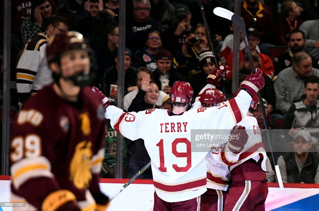Denver Pioneers forward Jarid Lukosevicius (14) celebrates his third goal with Denver Pioneers forward Dylan Gambrell (7) and Denver Pioneers forward Troy Terry (19) during the second period against the Minnesota-Duluth Bulldogs of the NCAA Men's Ice Hockey Championship on April 8, 2017 in Chicago, Illinois at the United Center.
