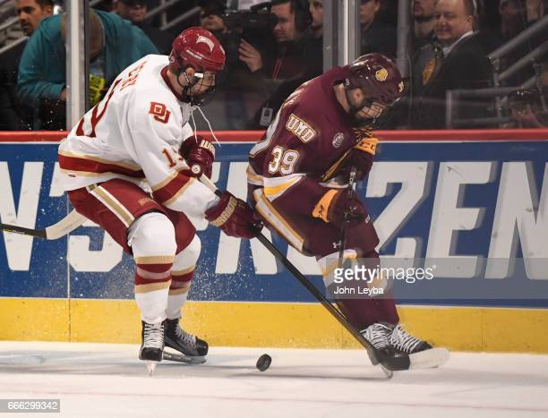 Denver Pioneers forward Troy Terry and MinnesotaDuluth Bulldogs forward Parker Mackay looks for the puck along the boards during the first period of...
