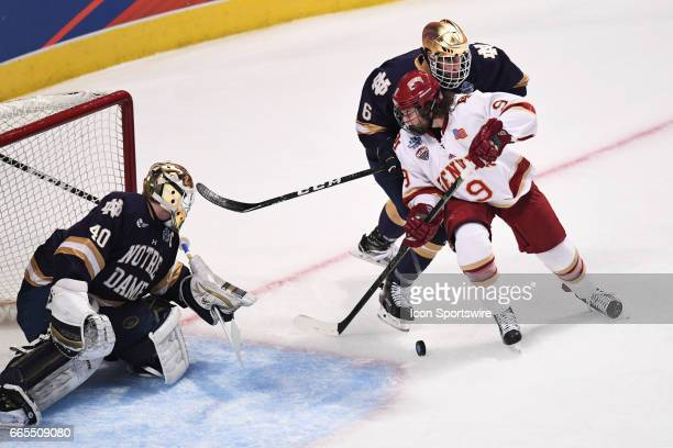 Denver Pioneers forward Tyson McLellan controls the puck against Notre Dame Fighting Irish goalie Cal Petersen and Notre Dame Fighting Irish...