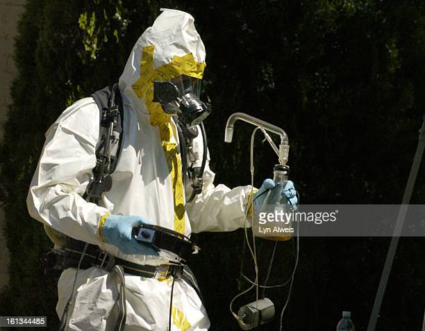 DENVER COLORADOJULY 18 2007A Denver Police Department vice narcotics officer dressed in a hazmat suit carries meth lab equipment from a home in the...