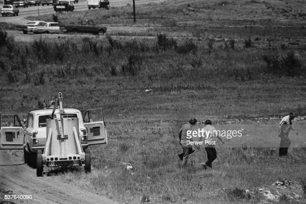 Denver Police Detectives C R Ferguson left and Joseph Erhart and Capt Robert Shaughnessy attach a rope to a bomb Wednesday as they work to defuse it...