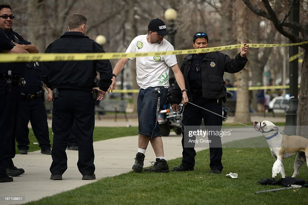 A Denver Police officer holds up police tape for a man and his dog at the southeast side of Civic Center Park after a shooting there Saturday afternoon, April 20th, 2013.