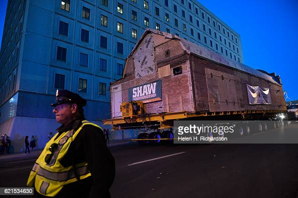Denver police officer Tony Montoya left clears the street as workers with Mammoth Moving and Rigging continue driving the 106 year old Kirkland Art...