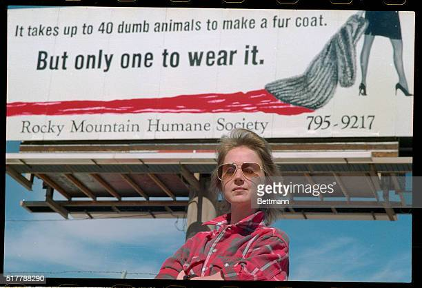 Robin T Duxbury executive director of the Rocky Moutain Humane Society stands in front of an antifur billboard featuring a woman dragging a fur...