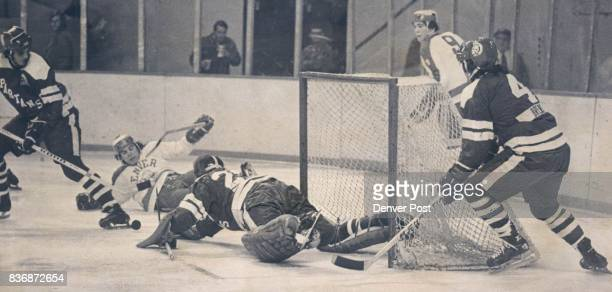 Denver University * Ice Hockey Puck proves Elusive Little Rascal after Spartan Goalie Makes a Diving Save Against Denver ***** State netminder Ron...