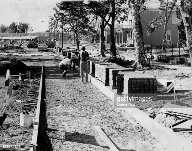 Denver Workmen lay flagstone paths after the street pavement was removed Road also will be sodded to create parklike link between houses in the Ninth...