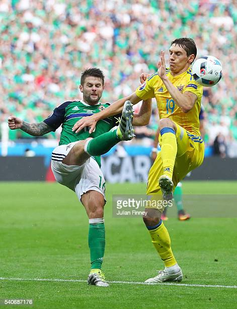 Denys Garmash of Ukraine and Oliver Norwood of Northern Ireland compete for the ball during the UEFA EURO 2016 Group C match between Ukraine and...