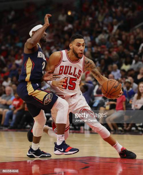 Denzel Valentine of the Chicago Bulls moves against Ian Clark of the New Orleans Pelicans during a preseason game at the United Center on October 8...